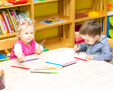 two toddlers playing with paper and pencil
