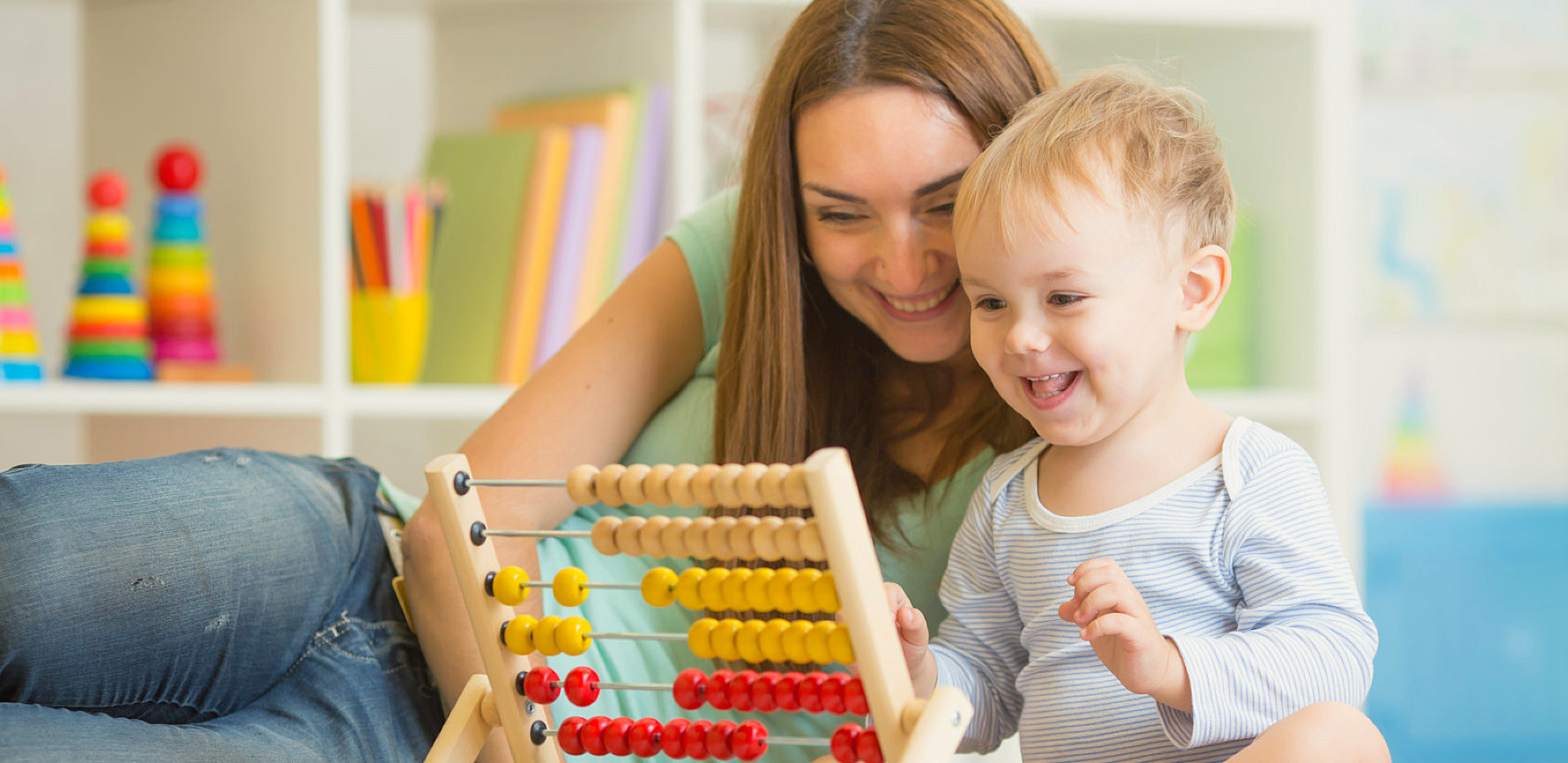 child with teacher playing abacus